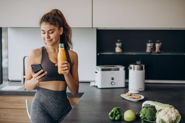Mulher esportiva na cozinha usando telefone celular Foto gratuita