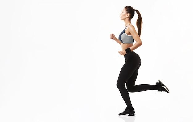 Mulher esportiva no treinamento sportswear correndo em branco. Foto gratuita