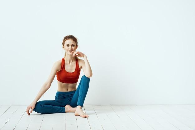 Mulher esportiva pose ginástica equilíbrio exercício luz de fundo. Foto Premium