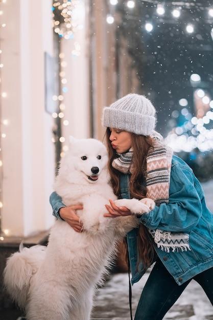 Mulher está abraçando seu cachorro em uma rua à noite Foto gratuita