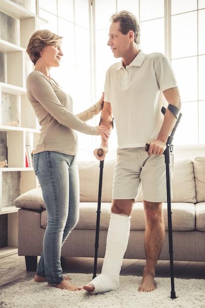 Mulher está ajudando seu marido bonito com a perna quebrada. Foto Premium