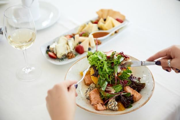 Mulher está comendo salada de porco com alface, conjunto de queijo e um copo de vinho Foto gratuita