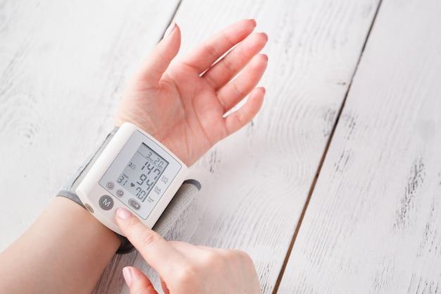 Mulher está cuidando da saúde com monitor de batimentos cardíacos e pressão arterial Foto Premium