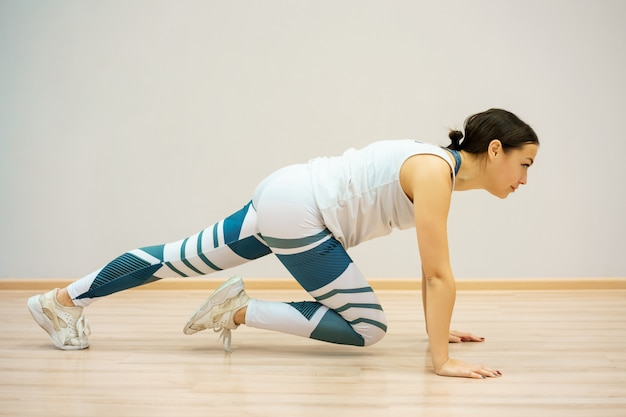 Mulher está envolvida em fitness em casa no tapete azul, em roupas esportivas. treino e alongamento em casa Foto Premium