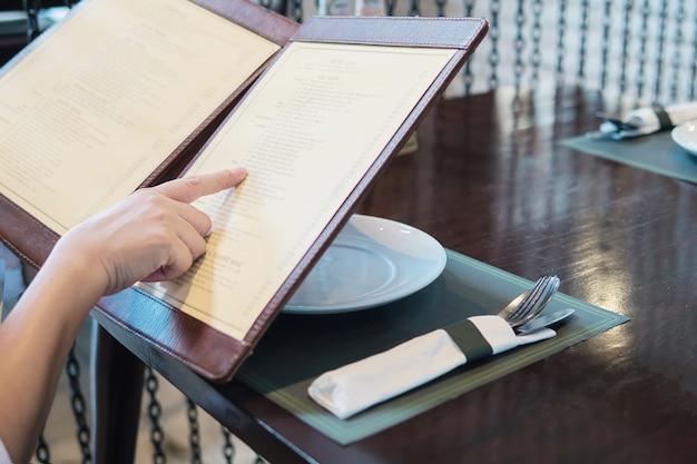Mulher está escolhendo comida em um menu para pedir no restaurante Foto gratuita