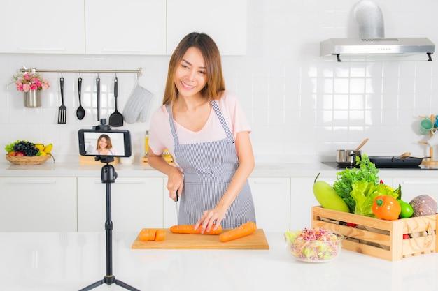 Mulher está gravando o vídeo de cozinha na cozinha. Foto Premium