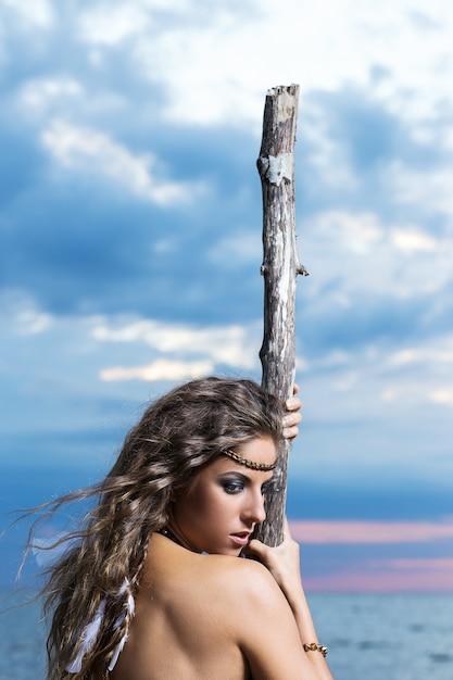 Mulher está posando com um pau Foto gratuita