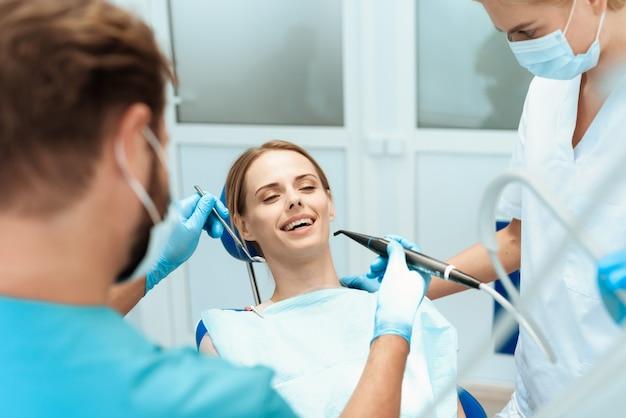 Mulher está sentada na cadeira odontológica, os médicos se inclinaram sobre ela Foto Premium