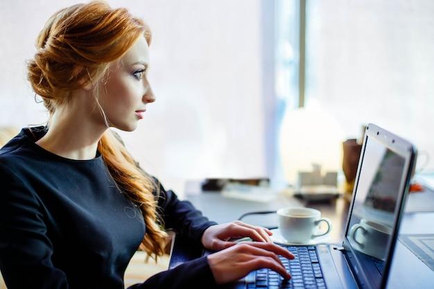 Mulher está trabalhando no laptop no café Foto Premium