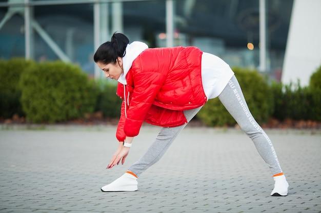 Mulher, esticando o corpo, fazendo exercícios na rua Foto Premium