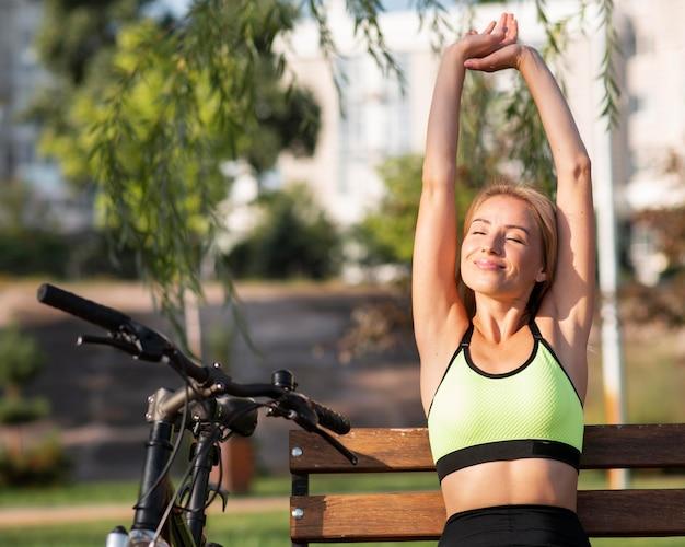 Mulher esticando os braços ao lado da bicicleta Foto Premium