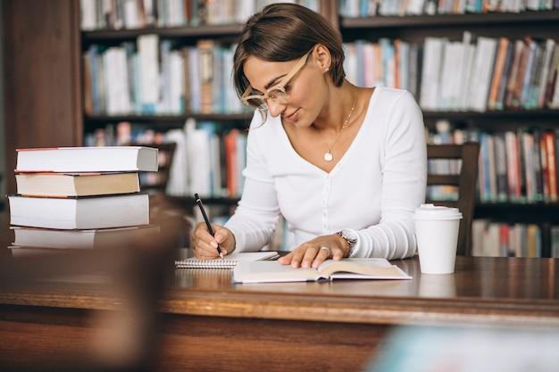 Mulher estudante estudando na biblioteca e bebendo café Foto gratuita