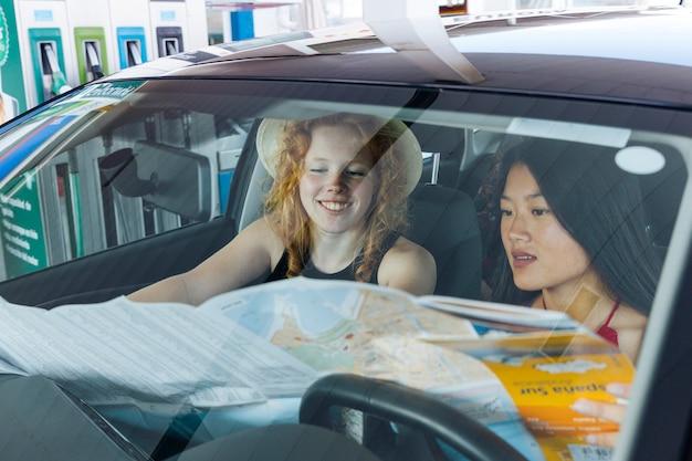 Mulher, estudar, mapa estrada, sentando, carro Foto gratuita