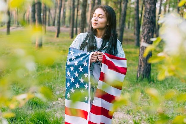 Mulher étnica com bandeira americana Foto gratuita