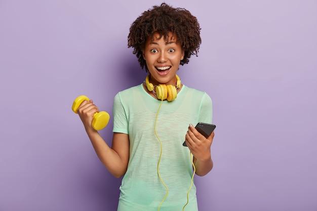 Mulher étnica encantada conversa no celular, ouve música durante os exercícios de jogigng, se aquece, segura halteres Foto gratuita