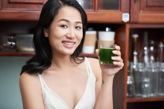 Mulher étnica sorridente com copo de suco Foto gratuita