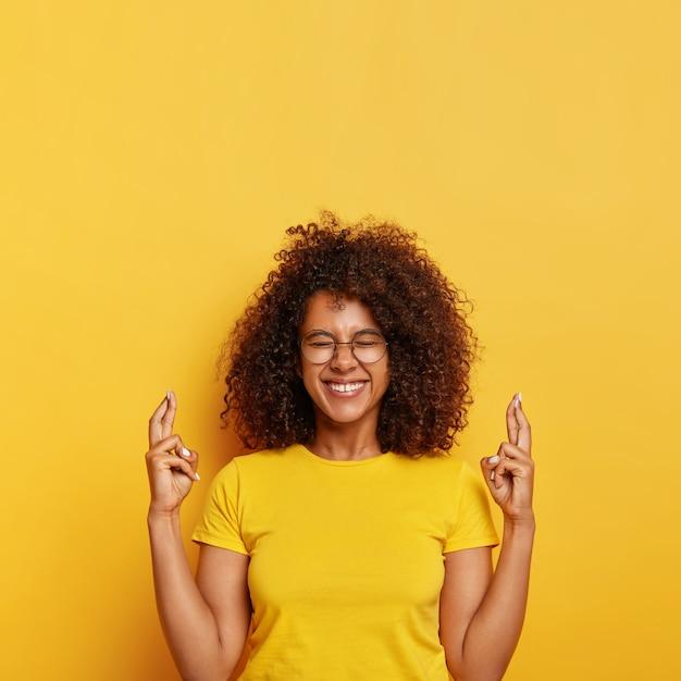 Mulher étnica supersticiosa alegre espera pelo melhor, cruza o dedo para dar sorte, ansiosa para conseguir uma posição em uma grande empresa, sorri com alegria, usa óculos e camiseta, isolada na parede amarela. Foto gratuita