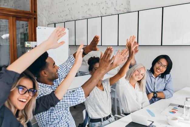 Mulher europeia atraente acenando as mãos com amigos, felizes por uma reunião bem sucedida. trabalhadores de escritório africanos e asiáticos se divertindo durante a conferência e rindo. Foto gratuita