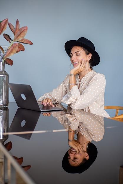 Mulher europeia com vestido e chapéu clássico trabalha em casa na cozinha Foto gratuita