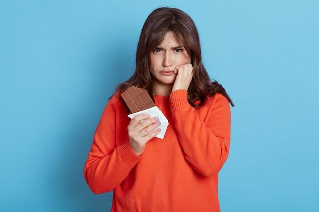 Mulher européia de cabelos escuros triste, vestindo traje casual posando isolada sobre a parede azul, olhando com expressão chateada, tem dor de dente, sofrendo de dor, mantendo o punho na bochecha. Foto Premium