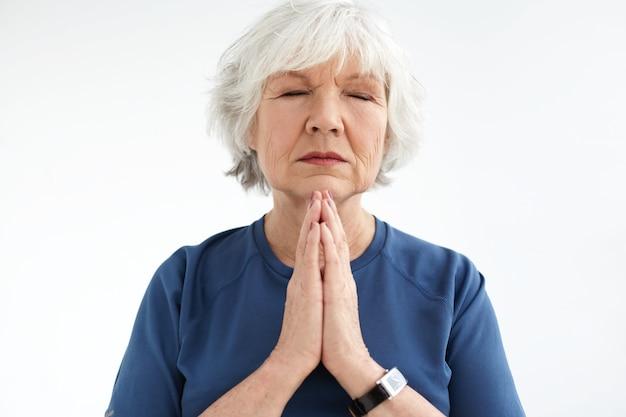 Mulher europeia de meia idade atraente com os olhos fechados, pressionando as mãos juntas em meditação. mulher sênior de cabelos grisalhos, apresentando expressões faciais pacíficas, praticando exercícios respiratórios e meditando Foto gratuita