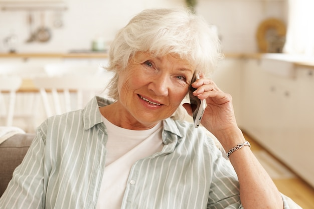 Mulher europeia idosa, madura, com camisa listrada, conversando ao telefone por meio de aplicativo on-line, usando a conexão gratuita à internet de alta velocidade sem fio em casa, olhando com um sorriso alegre Foto gratuita