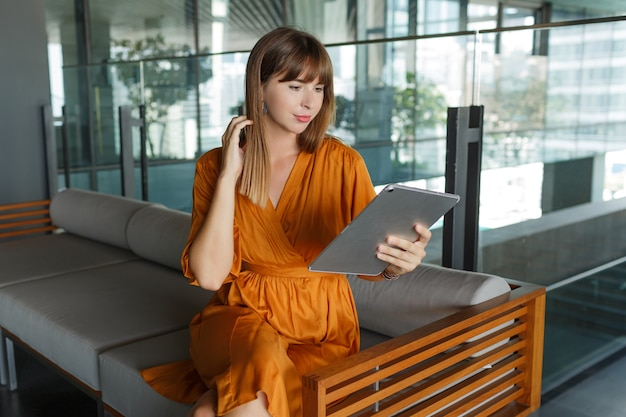 Mulher europeia pretti usando tablet em casa moderna, sentada no sofá. Foto gratuita
