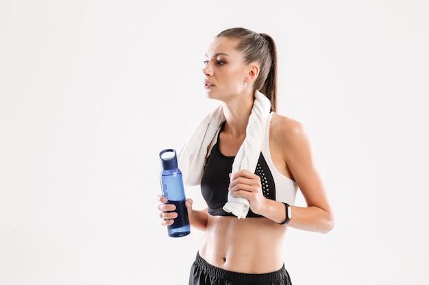Mulher exausta fitness suada com uma toalha no pescoço Foto gratuita
