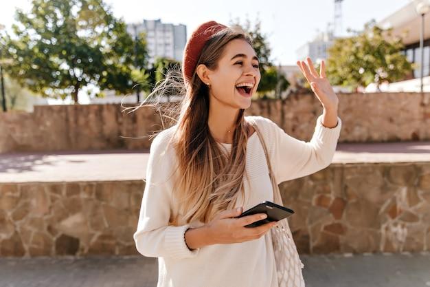 Mulher excitada em casaco de lã, posando na rua. menina atraente de cabelos compridos na boina vermelha, acenando com a mão. Foto gratuita