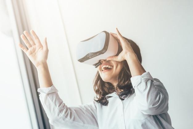 Mulher excitada se divertindo usando fone de ouvido de realidade virtual Foto Premium