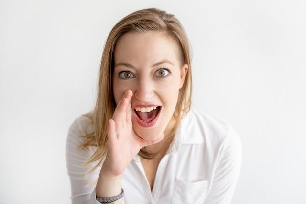 Mulher excitada segurando a mão perto da boca e gritando alto Foto gratuita