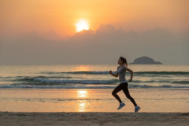 Mulher, executando, ligado, praia, em, amanhecer Foto Premium