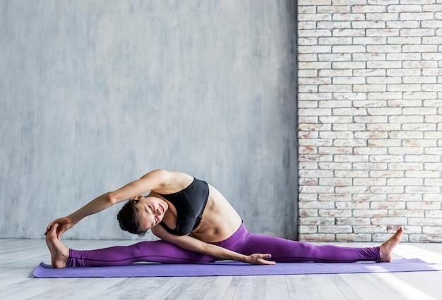 Mulher executando uma divisão lateral com o braço estendido Foto gratuita