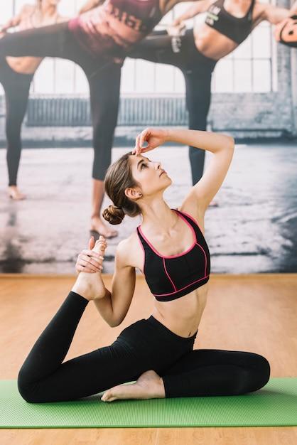 Mulher, executar, esticar exercício, em, estúdio aptidão, ligado, esteira verde exercício Foto gratuita