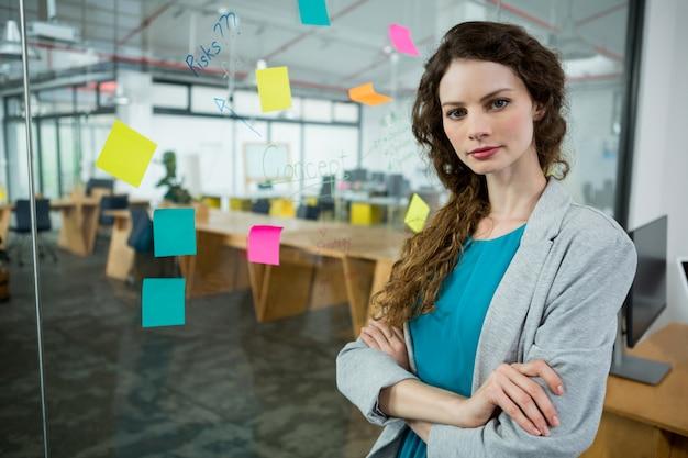 Mulher executiva confiante em pé com os braços cruzados no escritório  criativo | Foto Premium