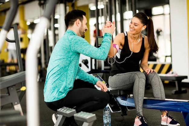 Mulher exercer em uma academia com a ajuda de seu personal trainer Foto Premium