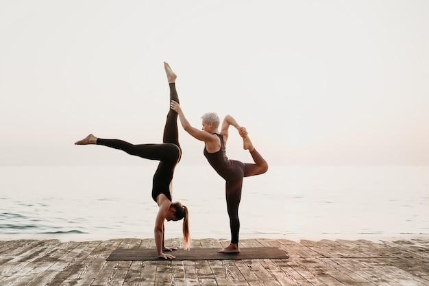 Mulher exercitando acro yoga na praia perto do mar pela manhã com o tutor feminino maduro Foto Premium
