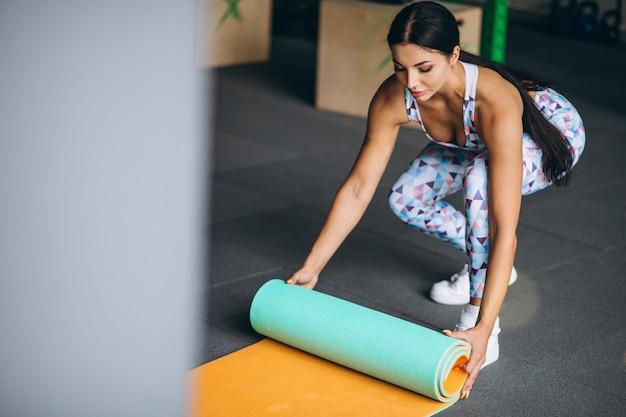 Mulher exercitando na academia segurando o tapete de ioga Foto gratuita
