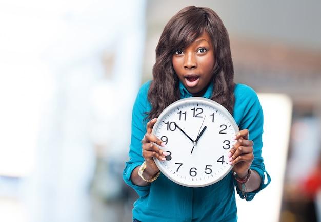 Mulher expressivo segurando um relógio Foto gratuita