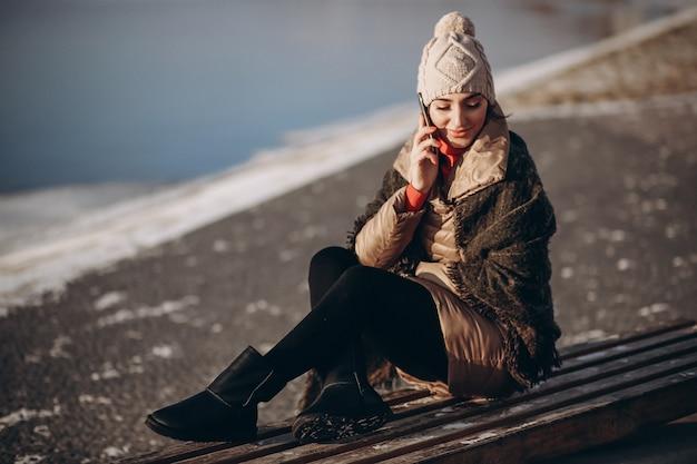 Mulher falando ao telefone e sentada em um banco junto ao lago Foto Premium