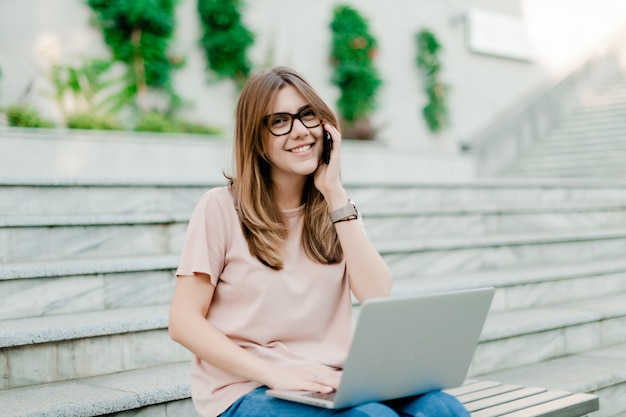 Mulher falando ao telefone e trabalhando no laptop ao ar livre Foto Premium