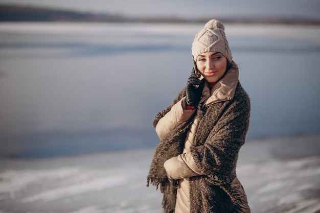 Mulher falando ao telefone no inverno pelo lago Foto Premium