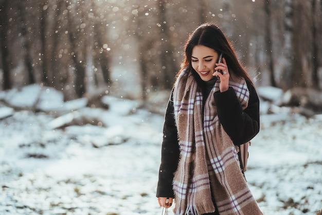 Mulher falando no celular em dia frio de inverno. Foto gratuita
