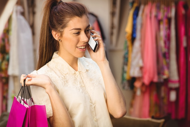 Mulher falando no celular enquanto fazia compras Foto gratuita