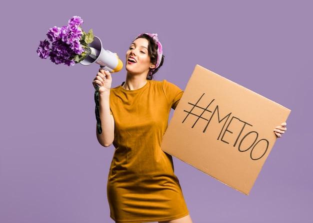 Mulher falando no megafone e segurando o cartão com sinal