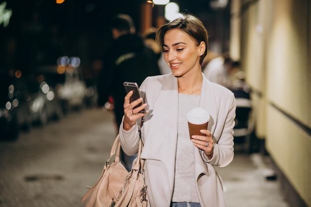 Mulher falando no telefone e tomando café lá fora na rua à noite Foto gratuita
