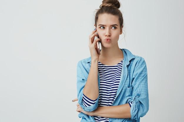 Mulher falando telefone ouvindo telefone quente rumores frescos fofocando animado intrigado, ouvindo notícias interessantes segurando smartphone pressionado orelha dobrar os lábios interessados olhando de lado, de pé Foto gratuita