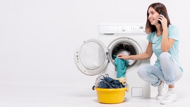 Mulher, falando, telefone, perto, lavadora roupa Foto gratuita