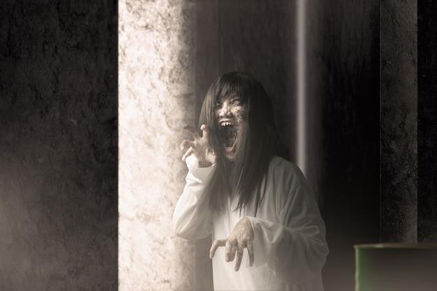 Mulher fantasma assustadora com sangue e cara feia com mãos arranhadas assombrou o prédio abandonado Foto Premium