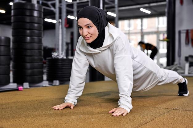 Mulher faz flexões. forte e em forma, atlética, muçulmana, exercitando-se sozinha em uma academia moderna. treino de treino, conceito de esporte Foto Premium